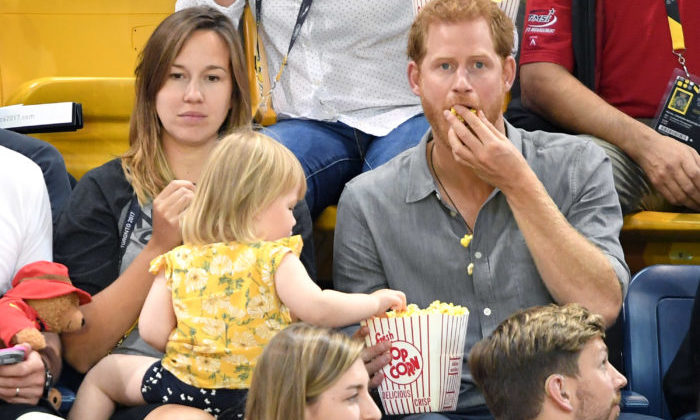 TORONTO, ON - SEPTEMBER 27:  Prince Harry with Hayley Henson, wife of British Paralympian Dave Henson and their two-year-old daughter Emily attend the Seated Volleyball on day 5 of the Invictus Games Toronto 2017 at Mattamy Athletic Centre on September 27, 2017 in Toronto, Canada.  The Games use the power of sport to inspire recovery, support rehabilitation and generate a wider understanding and respect for the Armed Forces.  (Photo by Karwai Tang/WireImage)